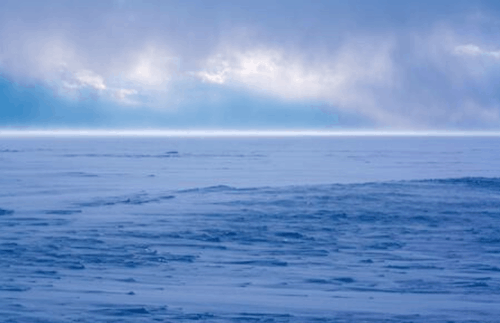 Photo of snowstorm approaching over frozen lake